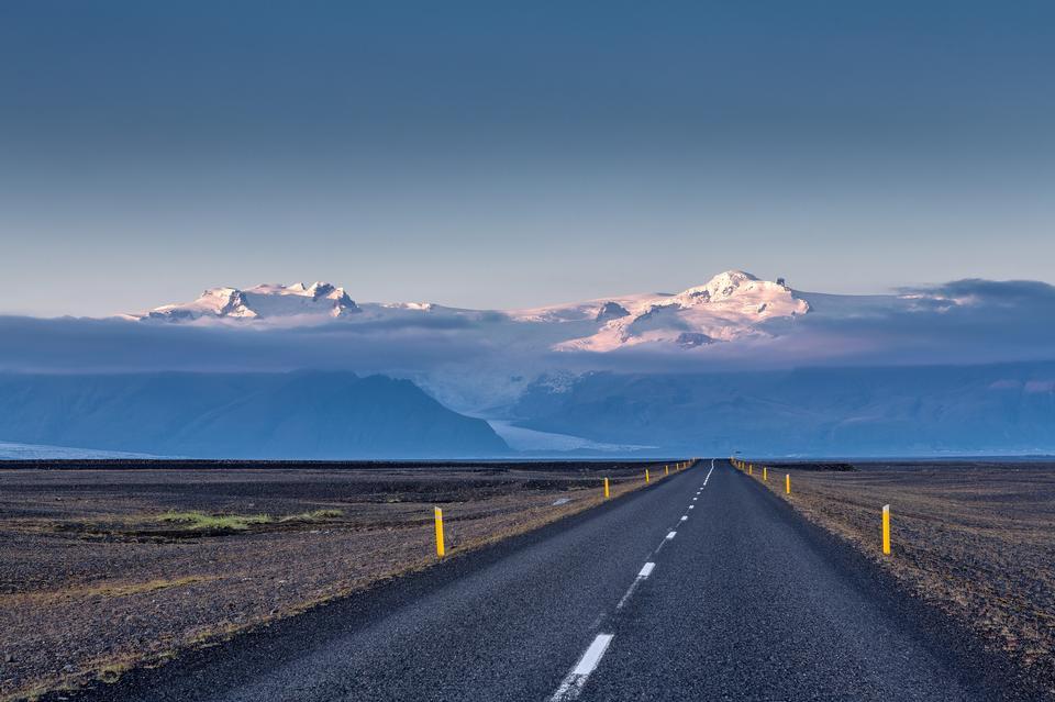 Leere Straße zum Schnee bedeckte Berge Island
