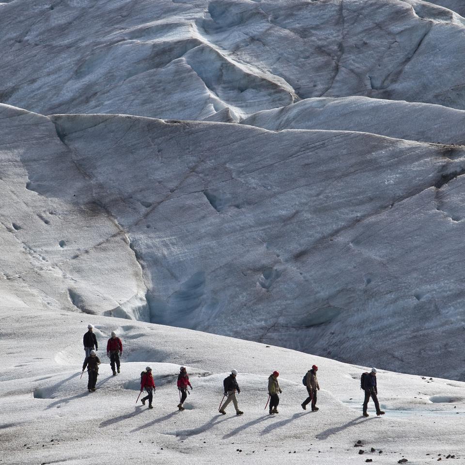 Group of people trekking on top of glacier