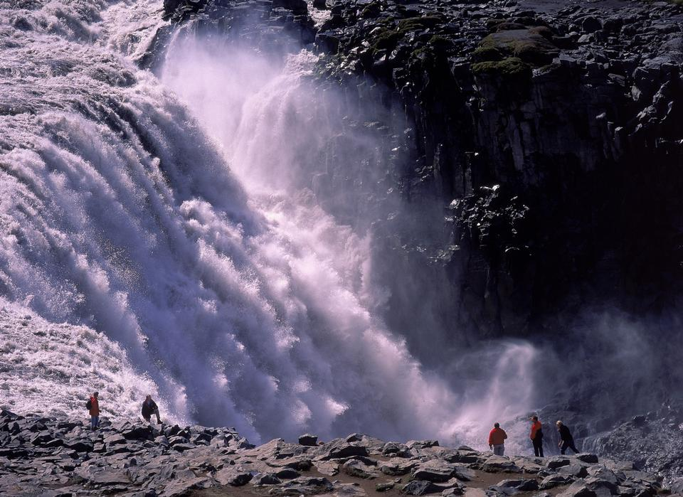 Tourist looking at the powerful waterfall of Dettifoss