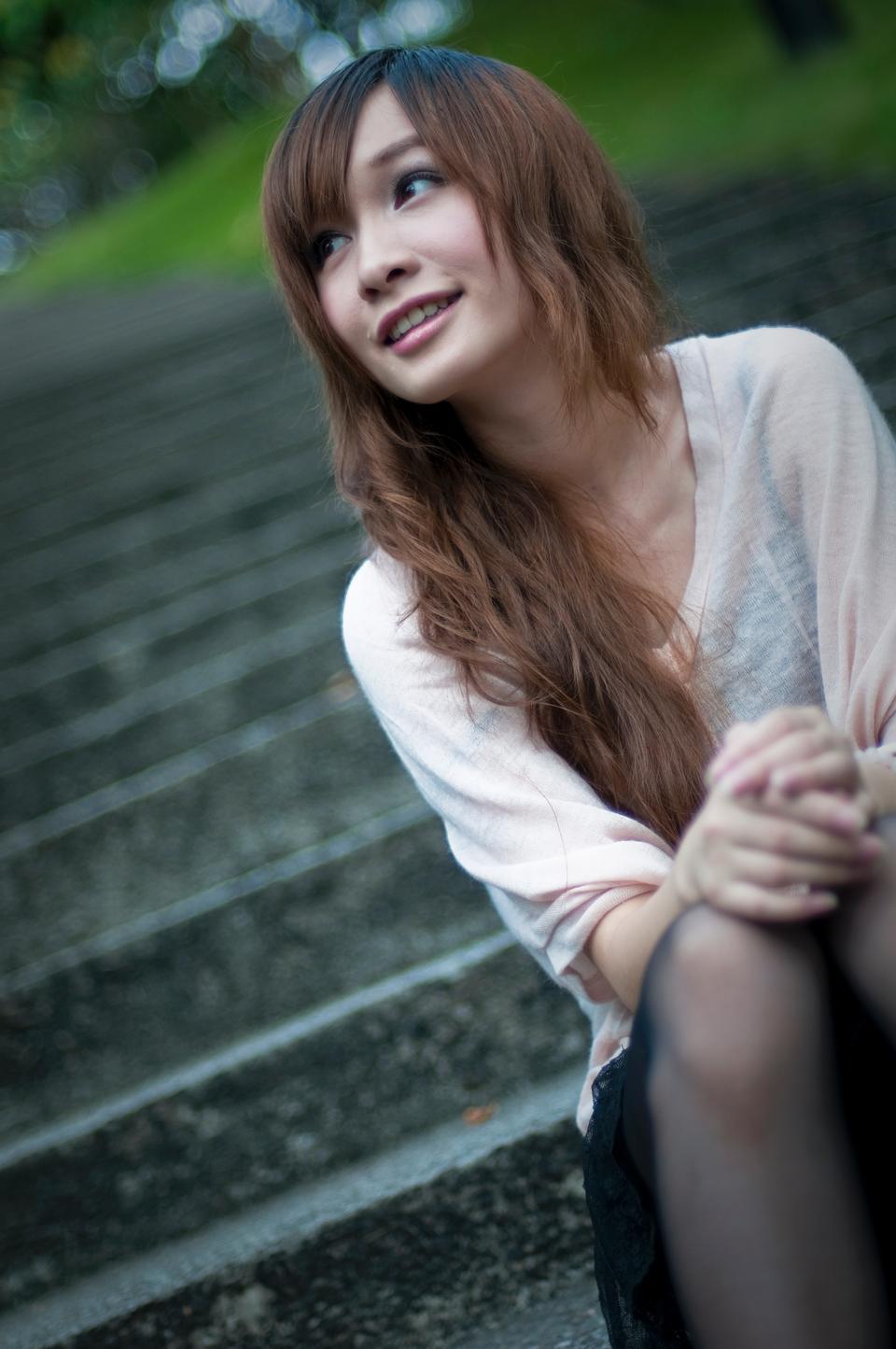 Chica linda que se sienta en pasos fuera