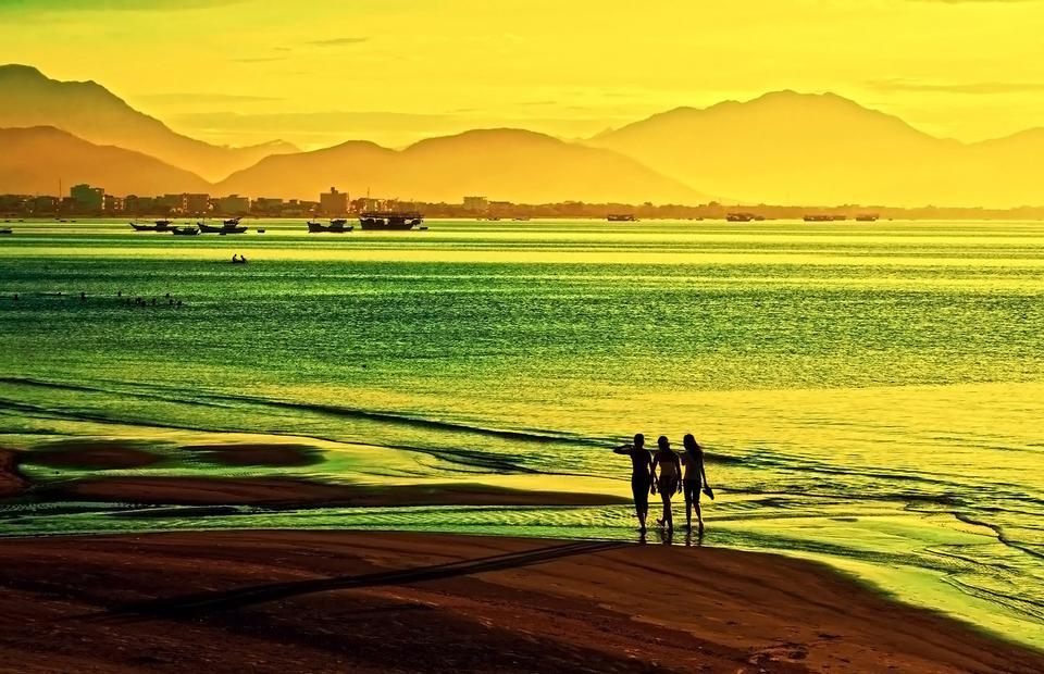 女性は日没で浜辺を歩く