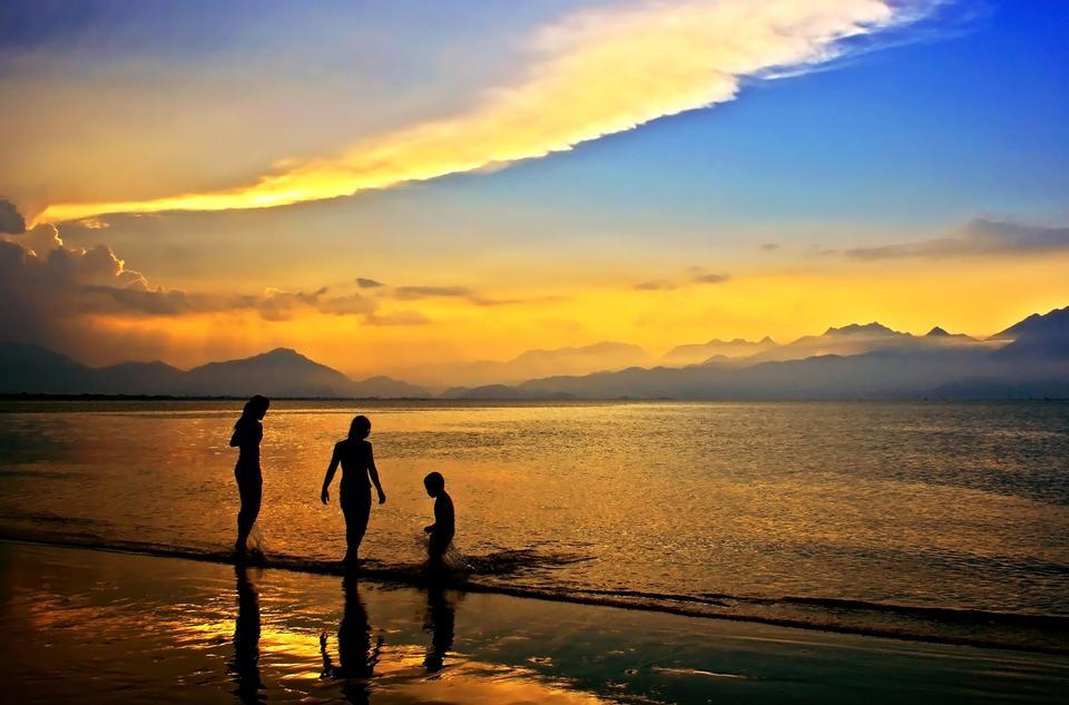Junge Frauen, die auf Strand im Abendlicht
