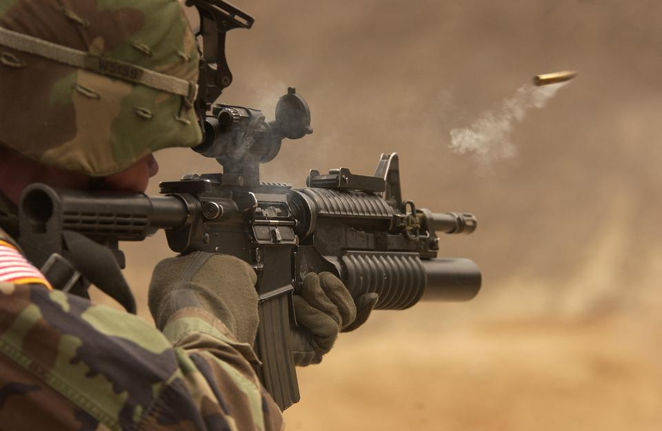 A shell casing flies out with a trail of smoke as U.S. Army