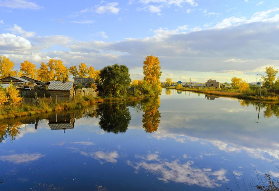 Деревья и небо отражается на спокойной воде. Осенний пейзаж