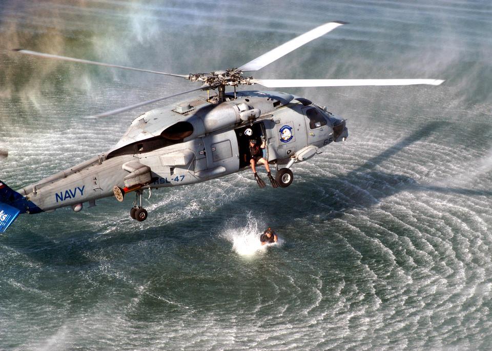 Una ricerca e soccorso (SAR) nuotatore prepara a saltare da un SH-60