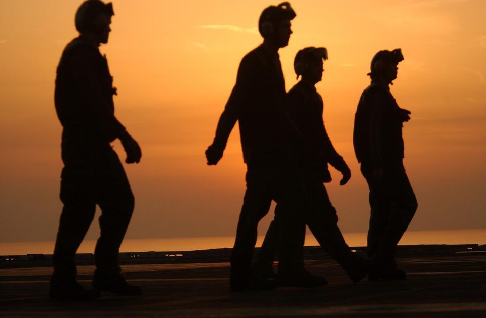 Crewmembers walk across the ships flight deck before the sun sets