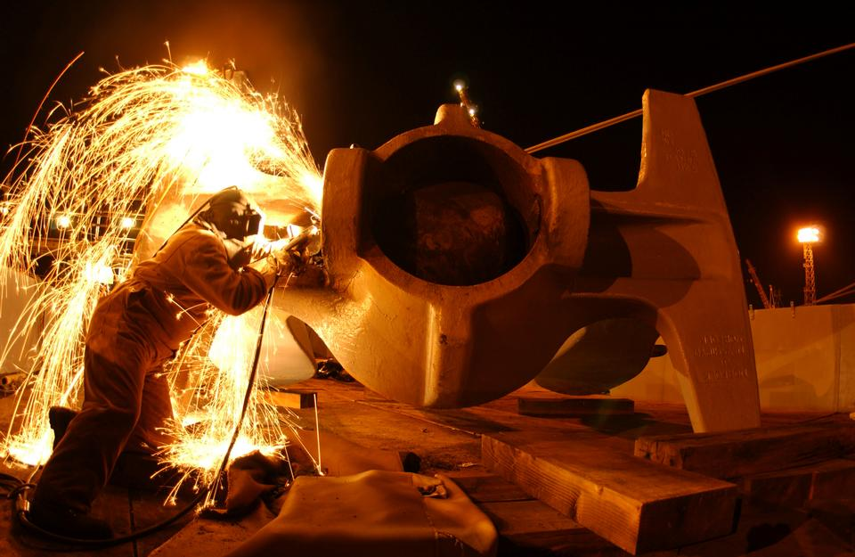 Sparks fly as a welder removes a cracked crown pin