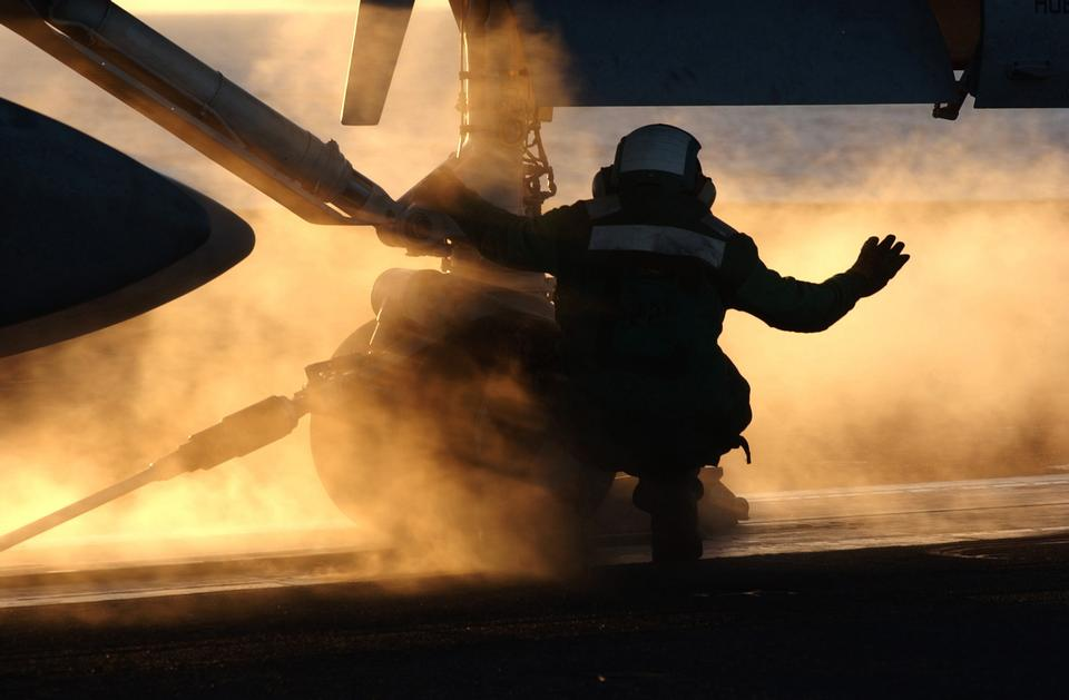 A catapult crewmember communicates by hand signals with flight d