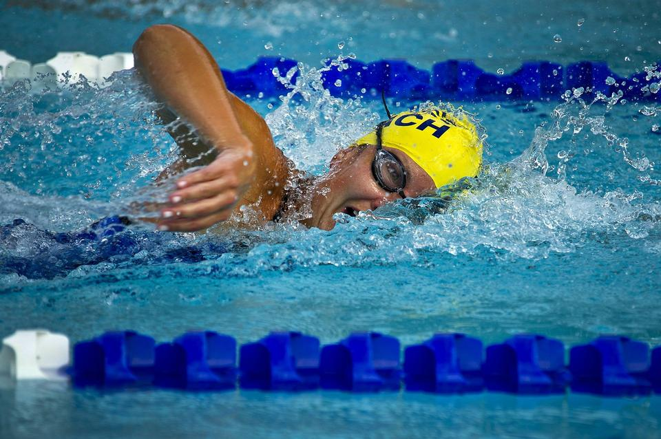 Young female swimming the front crawl in a pool