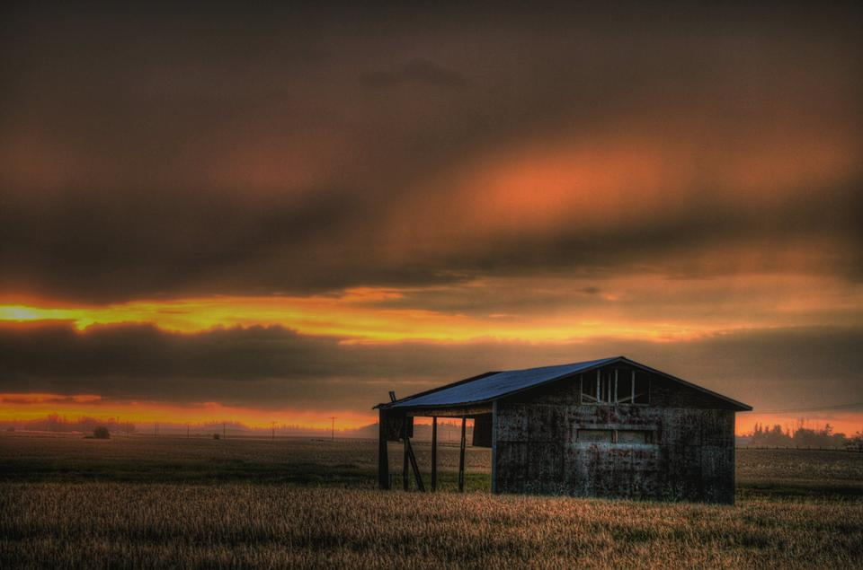 Sunset field and farmhouse inAlberta Canada