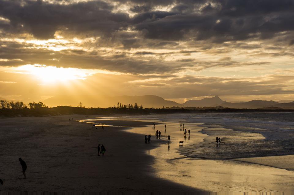 人站在海浪在夕阳滚滚海滩