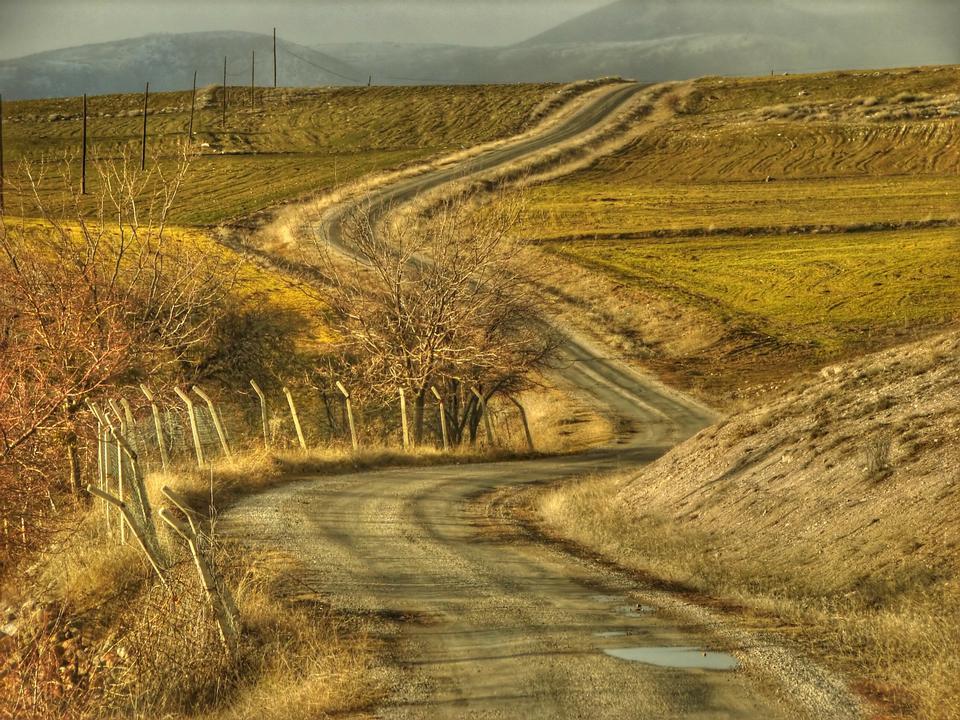 um caminho rural longa e sinuosa atravessa as colinas
