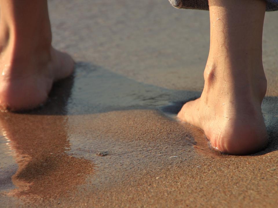 ビーチの少女のベアフット美脚