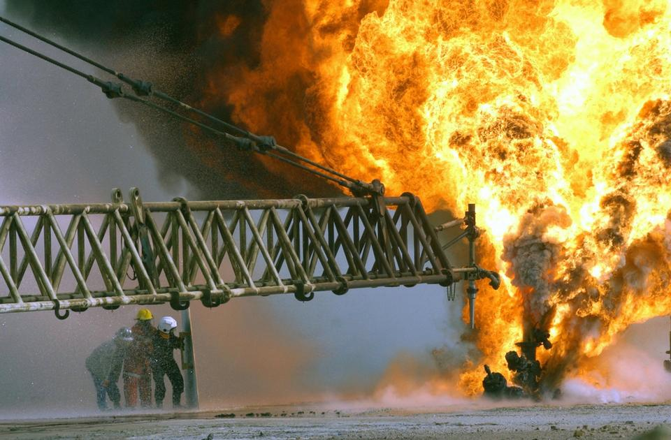 Kuwaiti firefighters fight to secure a burning oil well