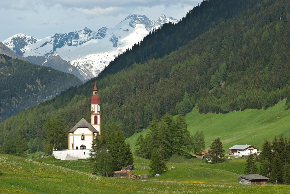 Red-steepled church surrounded by alpine