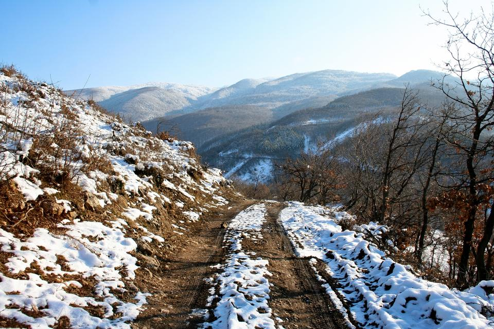 Rural unpaved road waving over the hills and mountains on a snowy