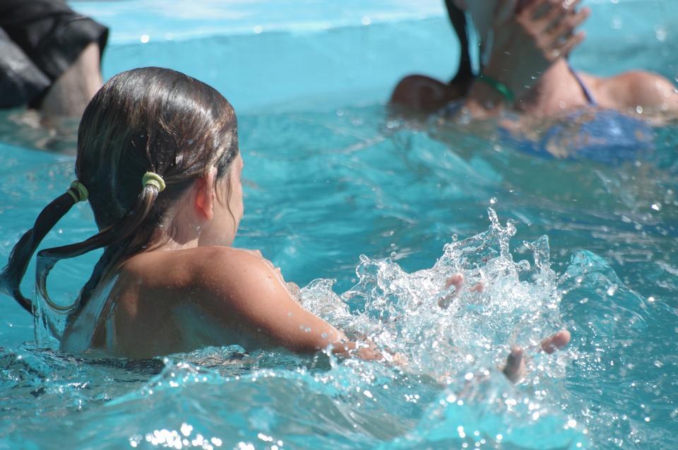 年轻的女孩游泳在游泳池