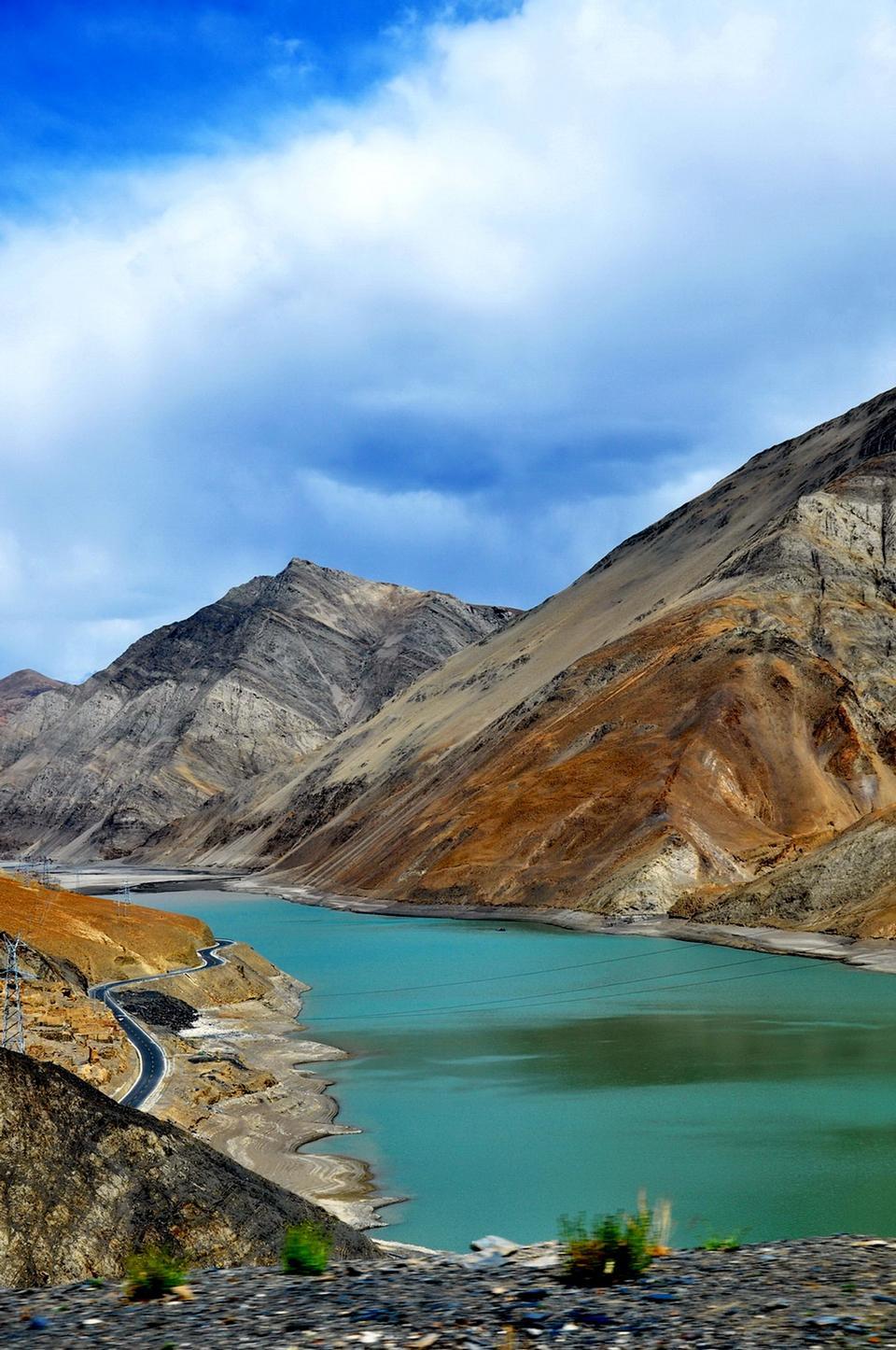 Yamdrok-TSOの湖がチベットで晴れた青空の日に輝く