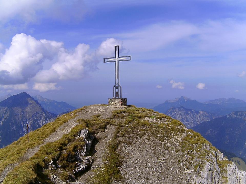 Каменный крест и распятие на старой часовни в горах