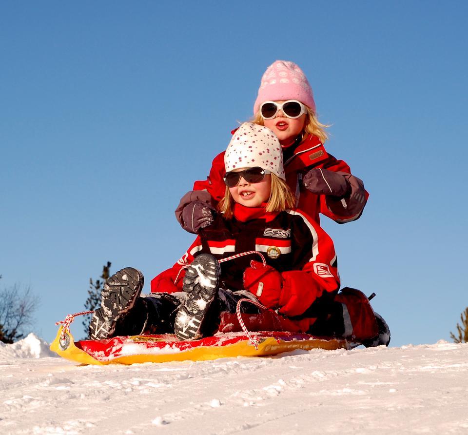kids sledding with a mountain