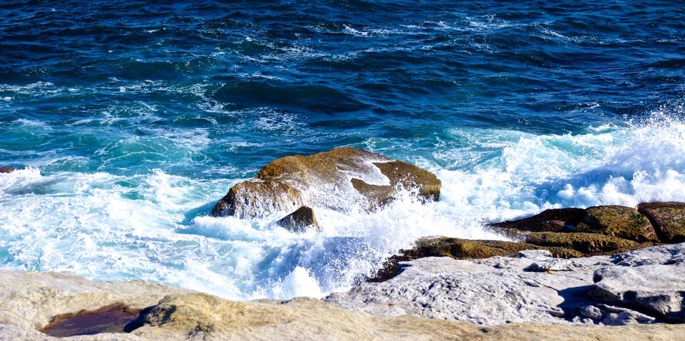 Caída de la onda Pequeño contra las rocas
