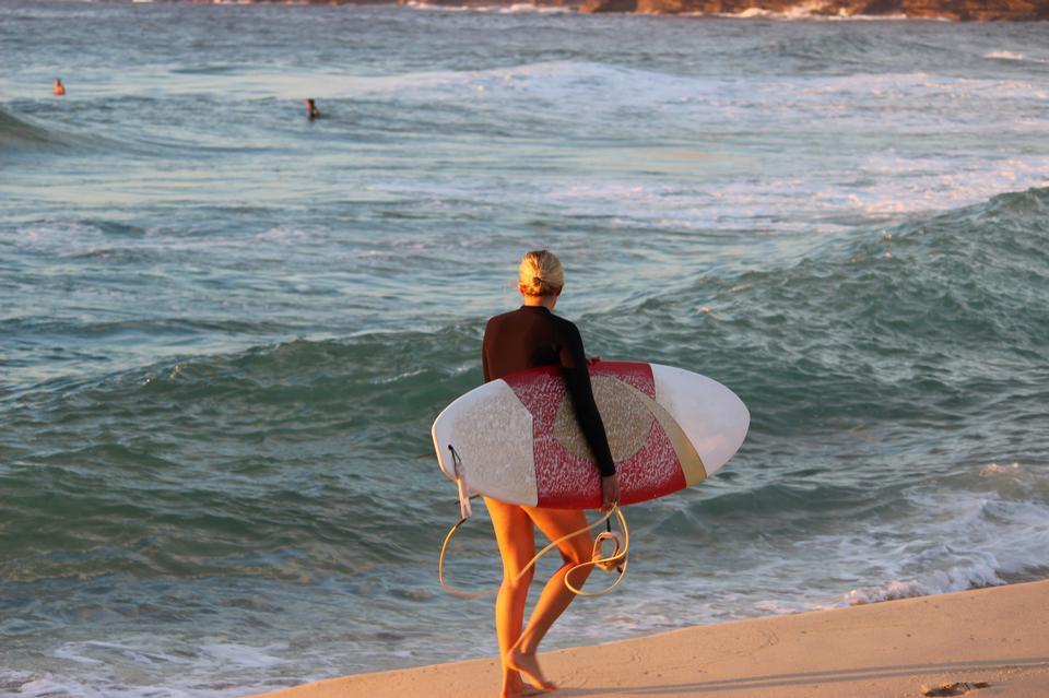 年輕漂亮的女子衝浪女孩在比基尼與白色的衝浪板