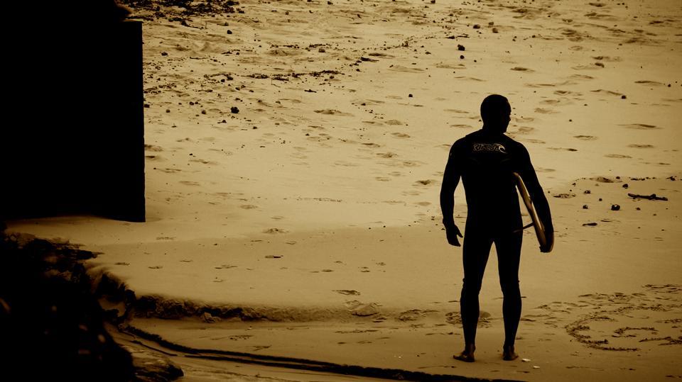 Puesta de sol en la playa con la observación de surfistas olas