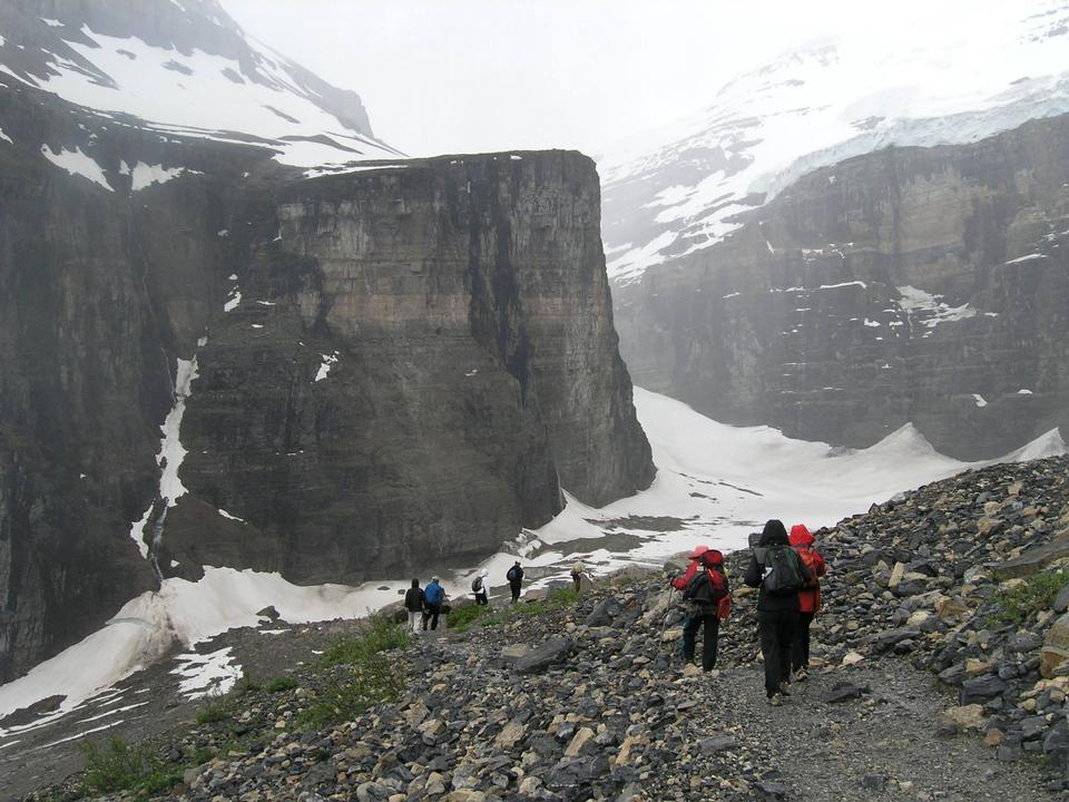 Hikers are climbing rocky slope of mountain