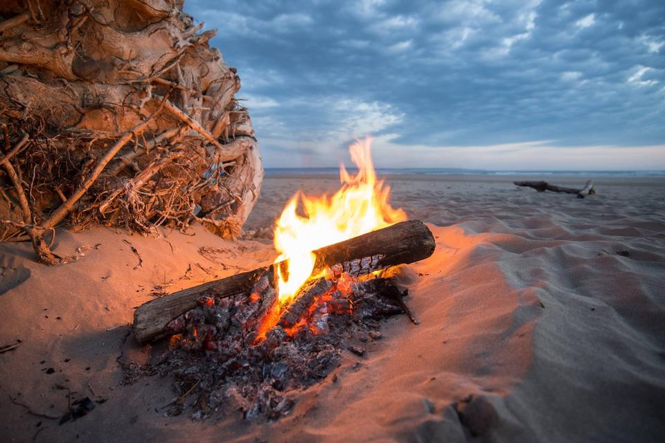 Beach campfire on lake with sand shore