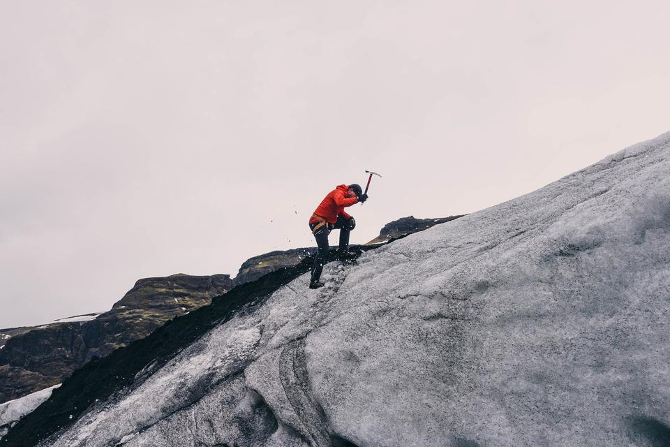 Climber ascending snowy peak at mountains