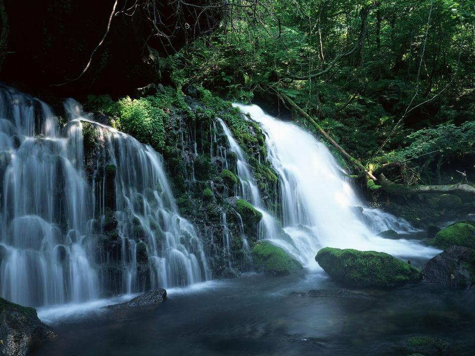 Waterfall rushing down the rocks, blue toning