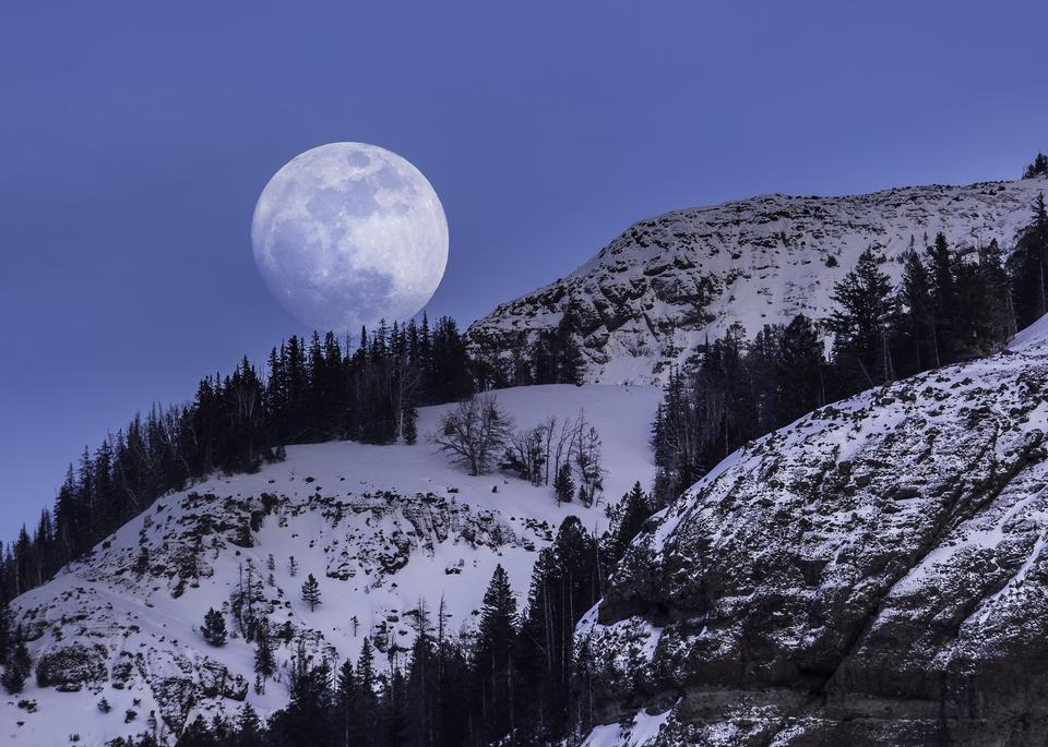 Full moon in the night sky in the mountains