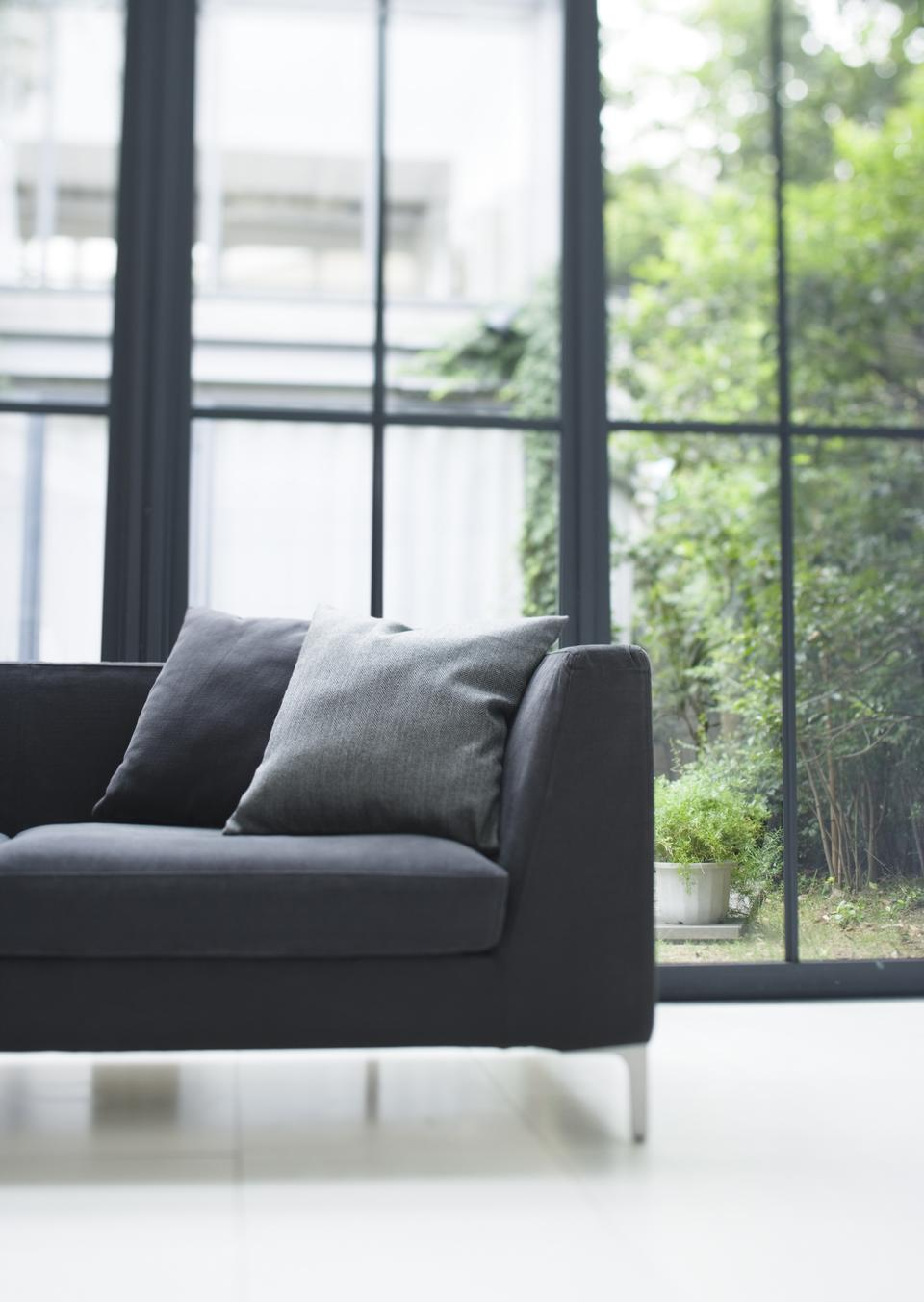 Comfy sofa with cushions against glass windows in the living room