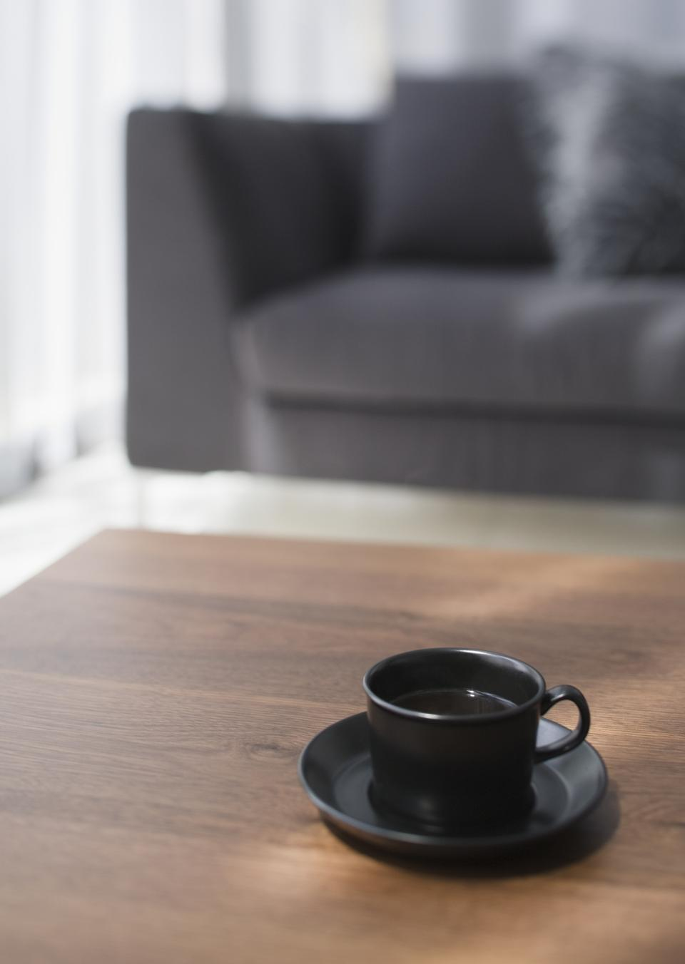 Black cup of coffee on table in living room