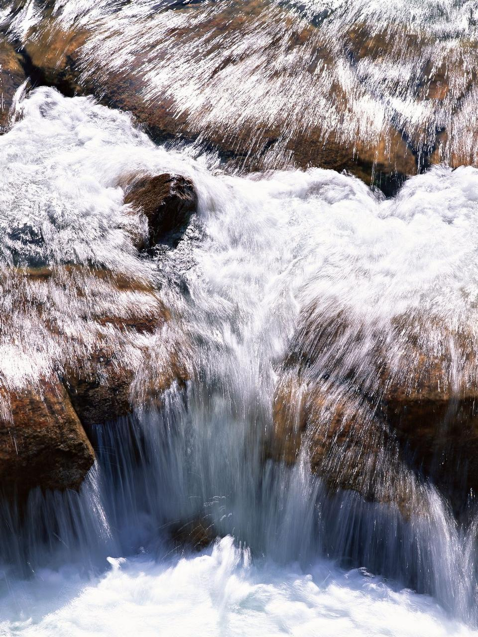 stones and mountain river with small waterfall, blurred backgroun