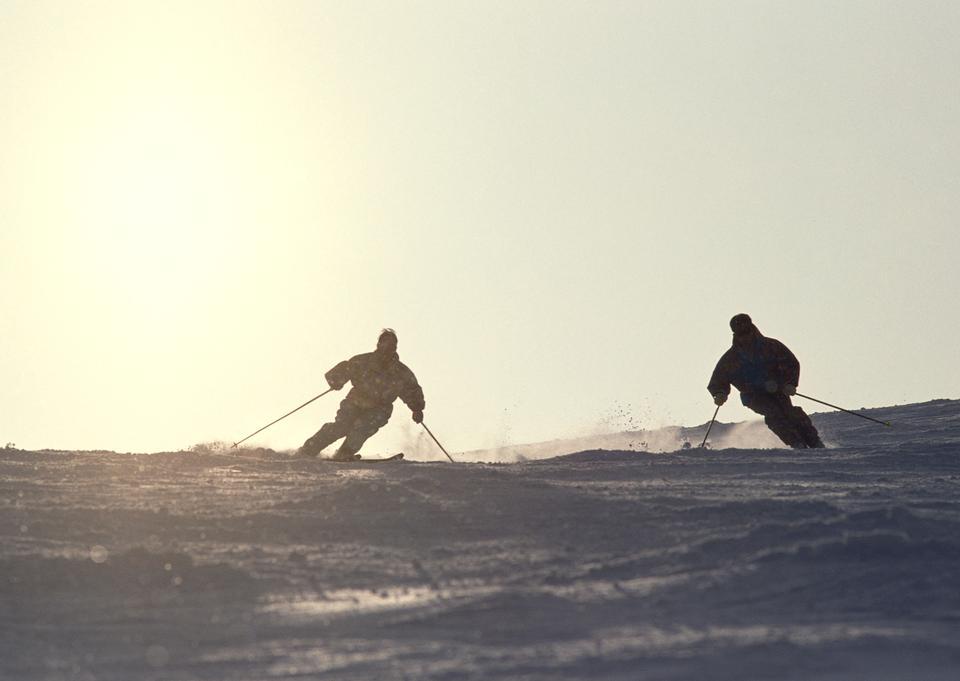 Silhouettes two guys on skis on the mountain