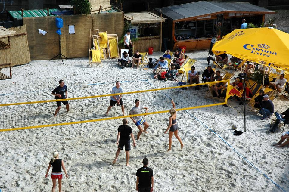 a group of young people playing volleyball on beach