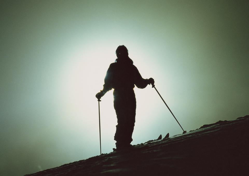Sciatore su un pendio al tramonto