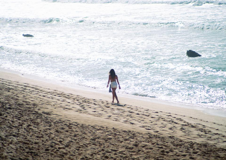Young woman walk on an empty wild beach