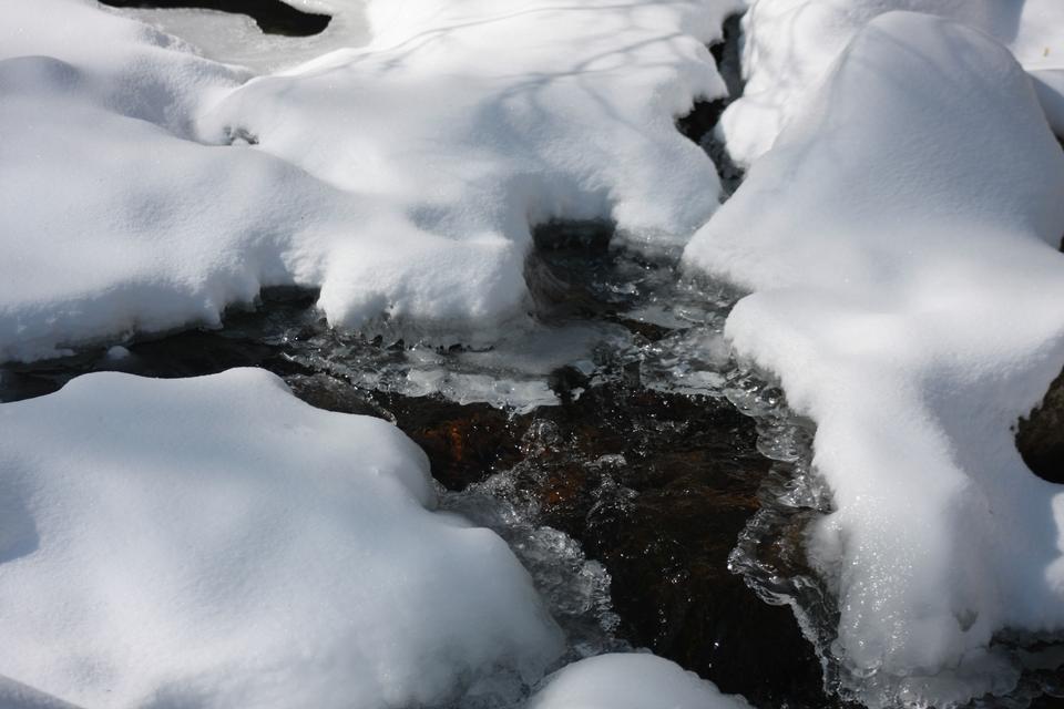 Petit cours d'eau partiellement couvert avec de la neige claire et fraîche