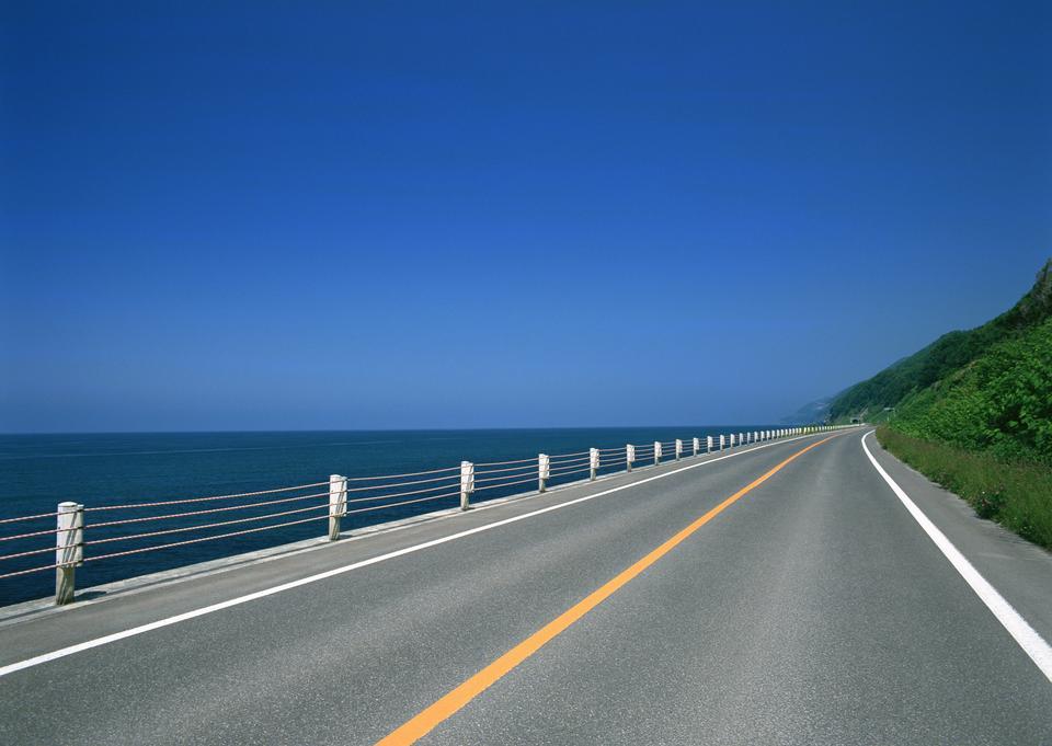 Mise route de montagne avec le ciel bleu et la mer