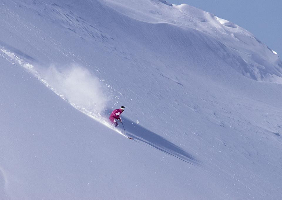 Alpine skier skiing downhill, blue sky