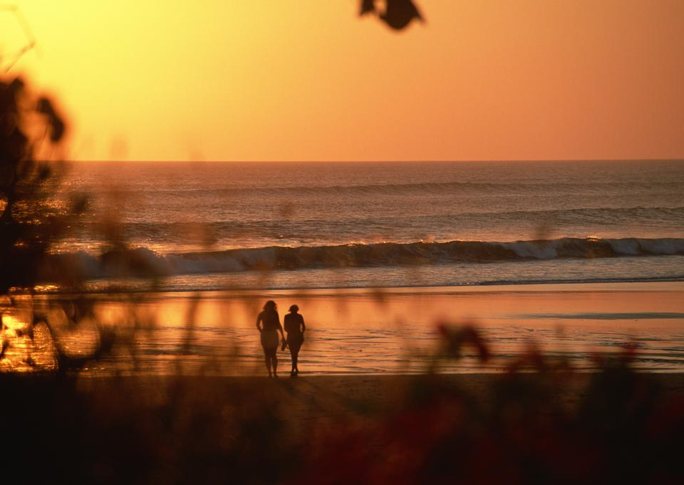 young happy couple at sunset beach