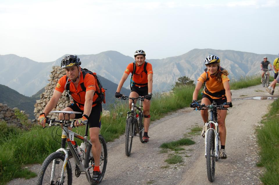 Three people are riding mountain bikes