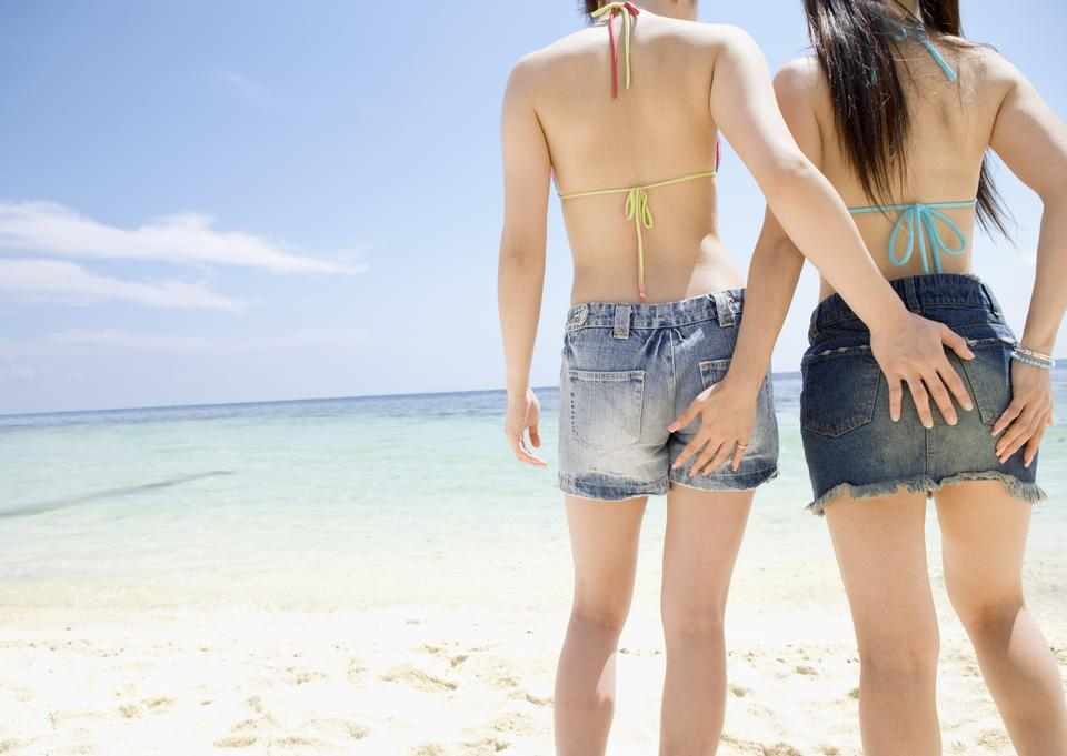 two beautiful young girlfriends at the blue sea and sky
