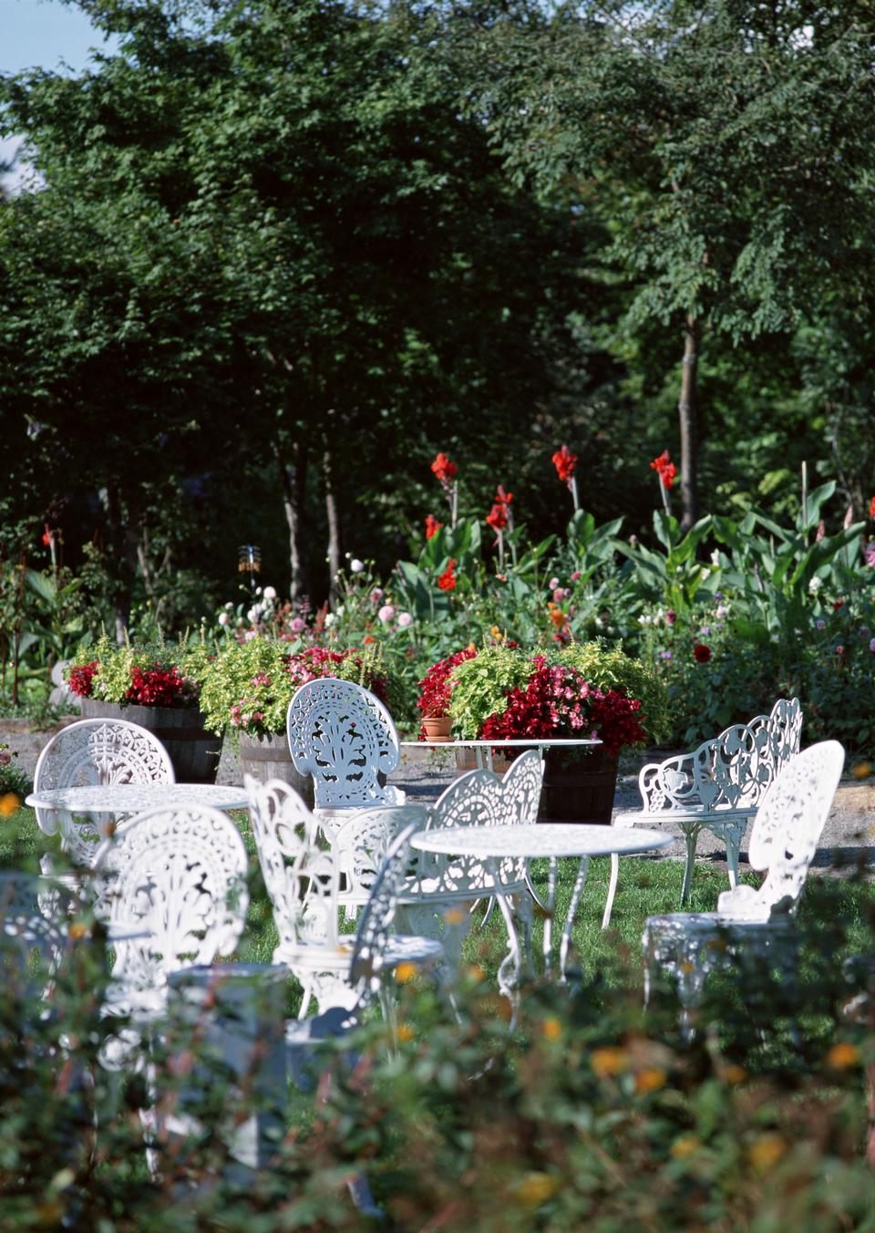 beautiful garden with white tea table and chairs