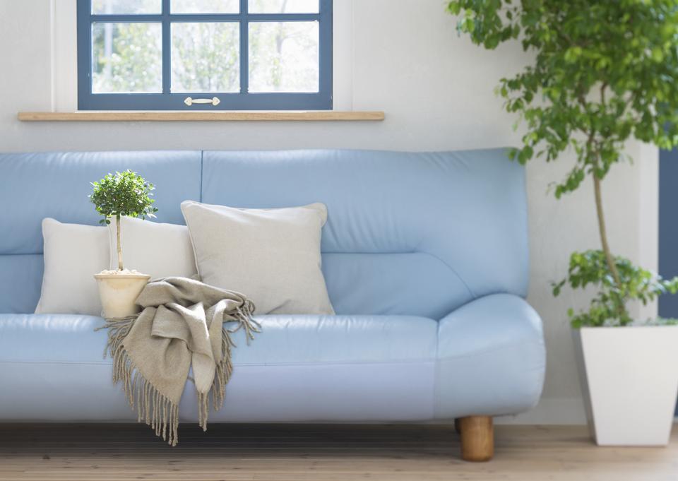 Интерьер гостиной с голубой диван и окна