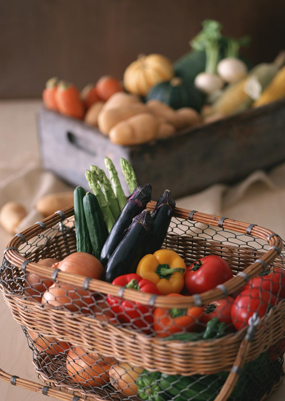 Assorted vegetables in basket on rustic wooden background.