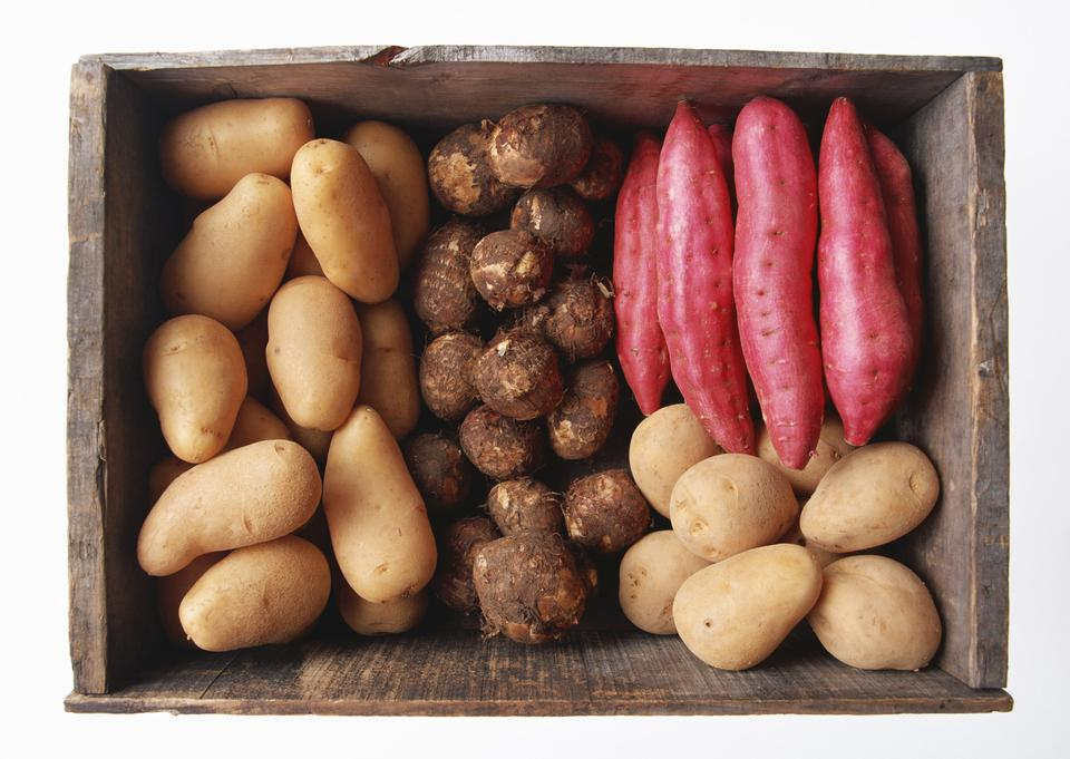 A variety of raw potatoes sweet potato and taro in wooden box