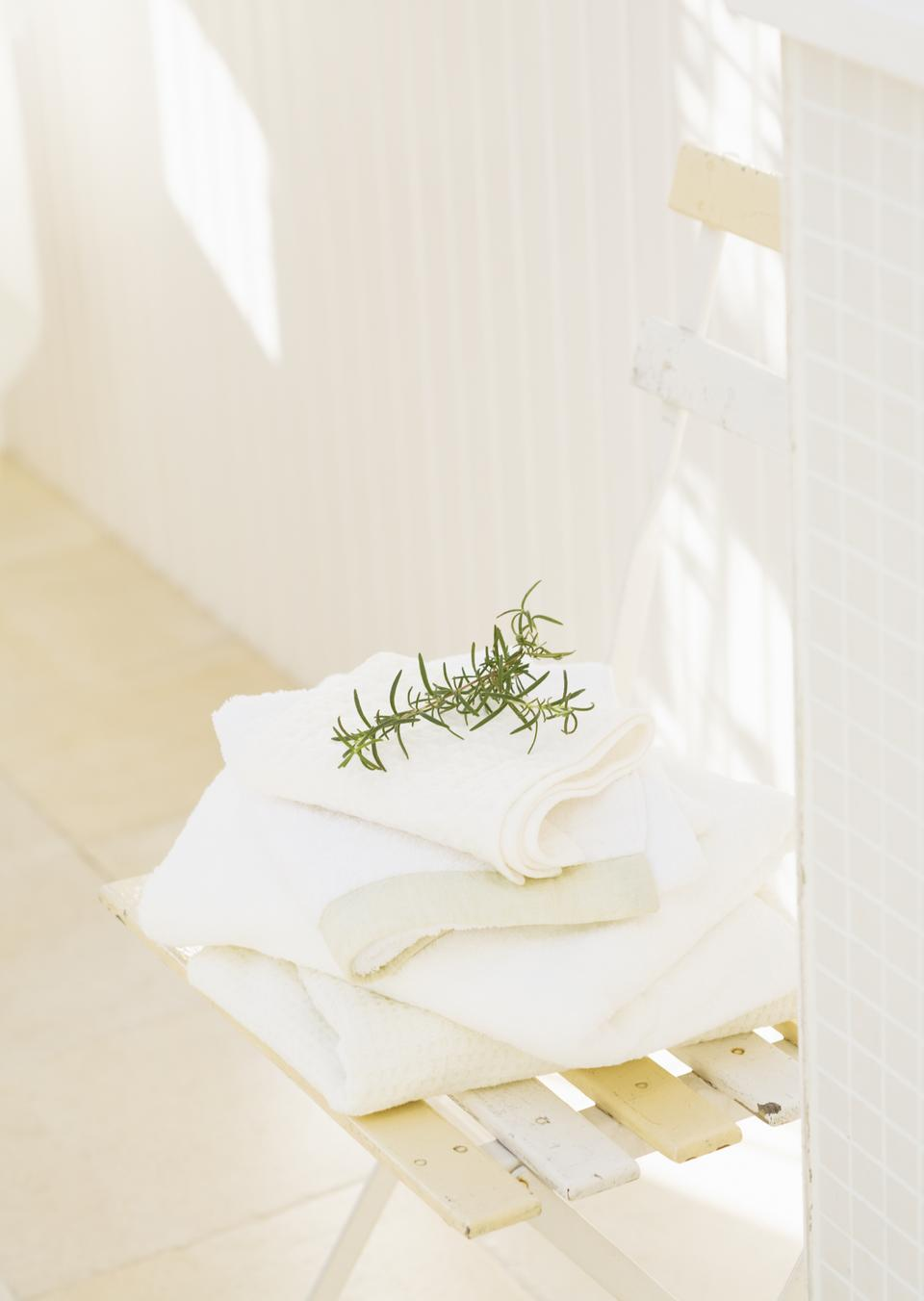 Branches of rosemary and  white towels on chair